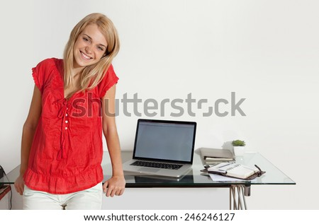 Attractive young student girl at her home office desk smiling while using a laptop computer against a white wall at home. Young professional woman workplace. First job and work experience, interior. - stock photo