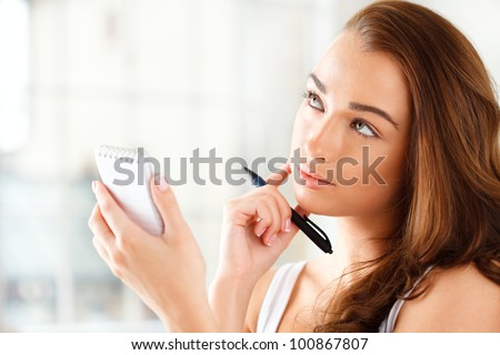 Attractive young student planning ahead - stock photo
