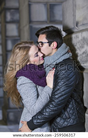 Attractive young stylish couple in love dressed in warm cloths outdoors. Boyfriend kisses his girlfriend  - stock photo