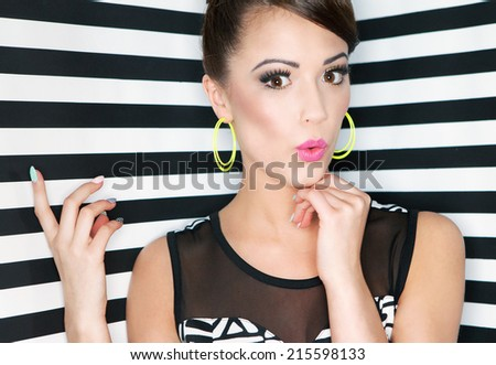 Attractive young surprised woman  on stripy background, pointing up, beauty and fashion concept  - stock photo