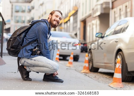 Attractive young tourist is kneeling and fastening shoe-laces. He is carrying backpack and camera. The man is looking forward and smiling. Copy space in right side - stock photo