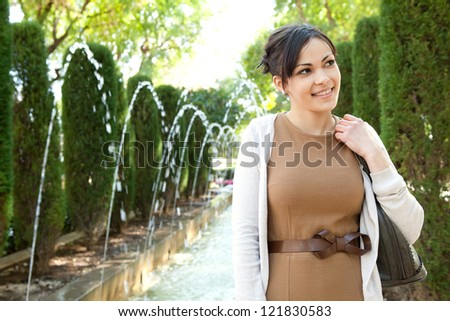 Attractive young tourist woman standing near a fountain in a botanic garden, holding her handbag, outdoors. - stock photo