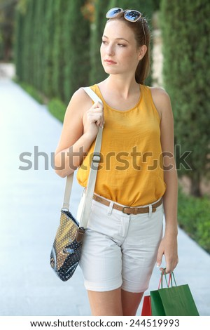 Attractive young tourist woman walking on a pavement by a green park in a destination city carrying shopping bags during a sunny summer holiday trip. Travel and lifestyle outdoors. - stock photo