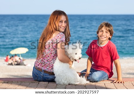 Attractive young woman and boy at the seaside with with cute white fluffy pet dog sitting on a wall overlooking the ocean turning to give the camera warm friendly smiles - stock photo