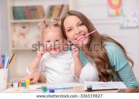 Attractive young woman and her small daughter are drawing with joy. They are holding pencils in their mouth and smiling. The mother and girl are sitting at the table at home - stock photo