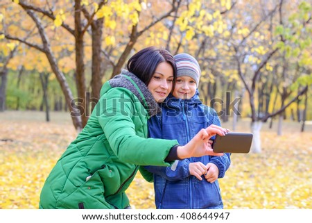 Attractive young woman and male child in cold weather clothes looking at phone in park surrounded by trees - stock photo