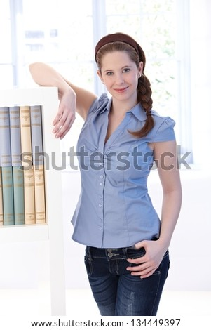Attractive young woman at home, standing by bookshelf, smiling at camera. - stock photo