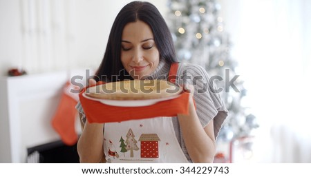 Attractive young woman baking tarts for Xmas standing in front of the Christmas tree savoring the aroma of a freshly baked pie - stock photo