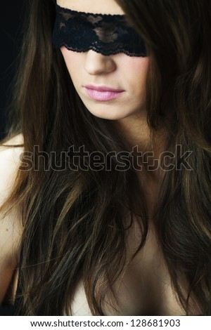 Attractive young woman blindfolded. Looking over her shoulder - stock photo