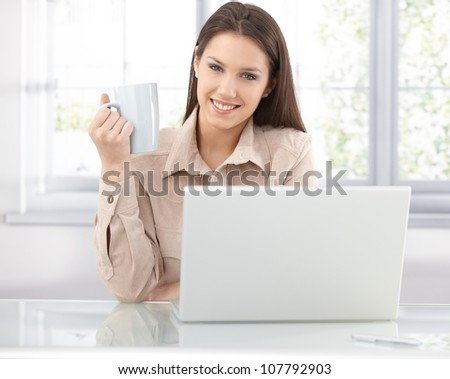 Attractive young woman browsing internet at home, using laptop, drinking tea, smiling. - stock photo