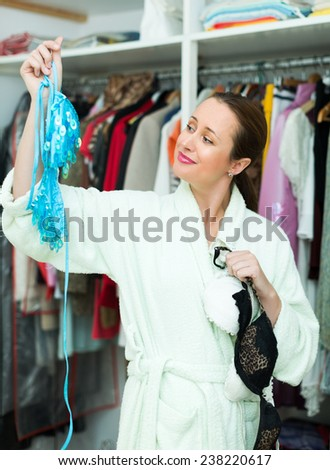 Attractive young woman choosing seductive underclothing at home - stock photo