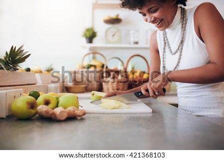 Attractive young woman chopping up fresh fruit for smoothie. Female working at juice bar. - stock photo
