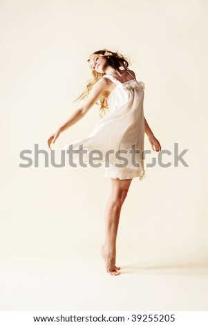 attractive young woman dancing, studio light background - stock photo