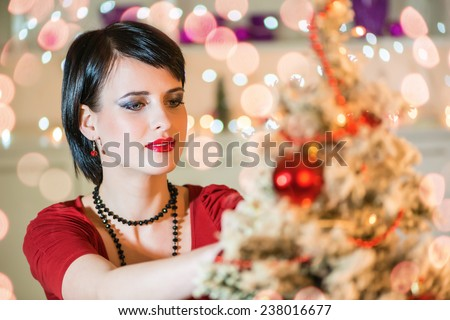 Attractive, young woman decorating the Christmas tree.Bokeh light, shallow doff.Copy space - stock photo