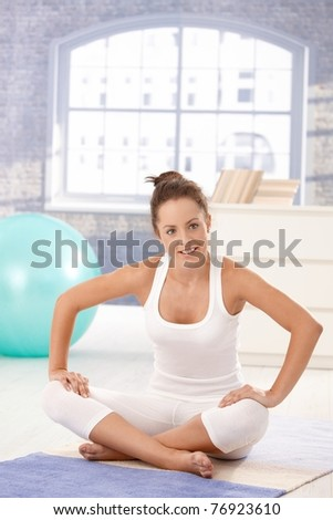 Attractive young woman doing exercises on floor at home, smiling.? - stock photo