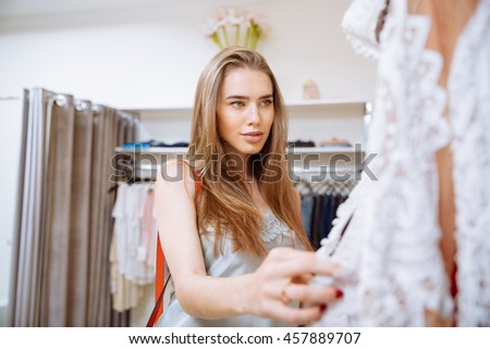 Attractive young woman doing shopping and choosing clothes in clothing store - stock photo