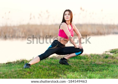 Attractive young woman doing yoga near lake at sunset - stock photo