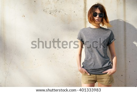 attractive young woman dressed in a gray blank t-shirt posing on a background of a concrete wall in the rays of the setting sun - stock photo