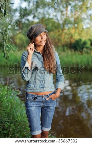 Attractive young woman dressed in jean and beret - stock photo