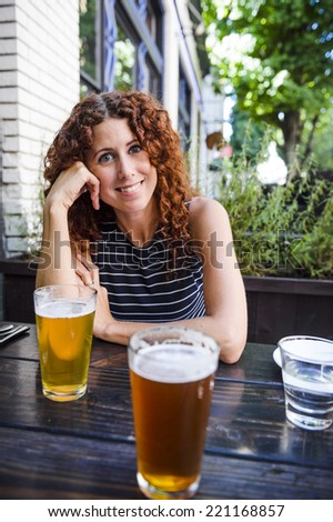 attractive young woman drinking beer at outdoor pub - stock photo