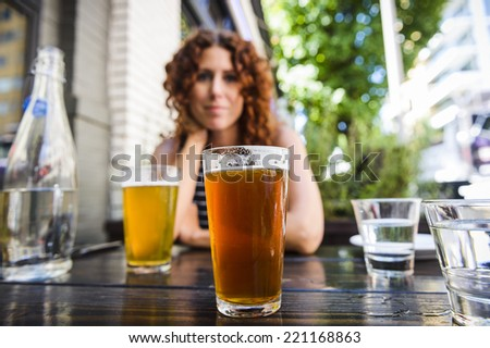 attractive young woman drinking beer at outdoor pub.  focus on glass of beer. - stock photo