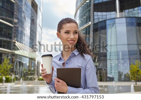 Attractive young woman drinking coffee and reading her touchscreen tablet while standing outside a commercial building - stock photo