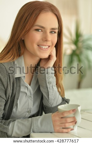 Attractive young woman drinking tea - stock photo