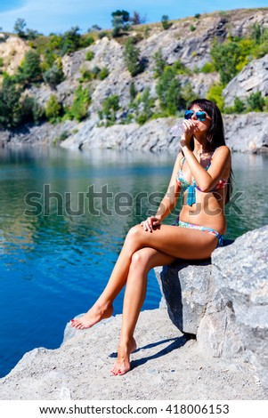 attractive young woman drinking water sitting on a rocks on a background of mountain river at sunny summer day. - stock photo