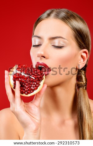 Attractive young woman eating fresh pomegranate. Sexual lips, red lipstick. Healthy food concept. Red background. - stock photo