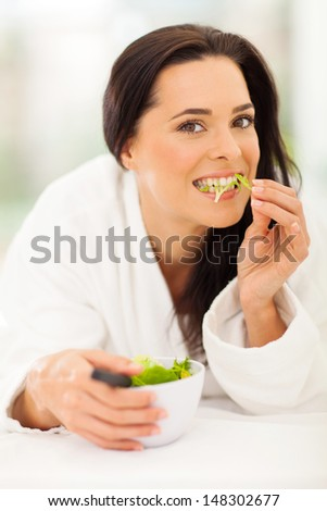 attractive young woman eating salad on bed - stock photo