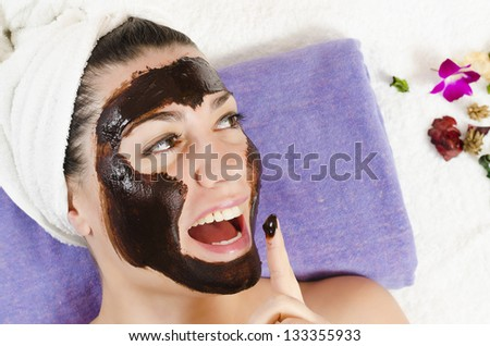 Attractive young woman getting a chocolate facial mask in the beauty spa - stock photo