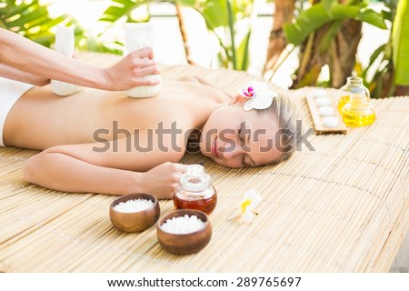 Attractive young woman getting massage on her back at spa center - stock photo