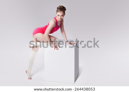 attractive young woman gymnast on a white cube, place for text - stock photo