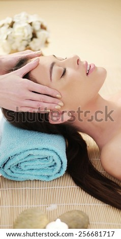 Attractive young woman having a head massage in a spa smiling with enjoyment as the masseuse massages her temples with her fingertips - stock photo