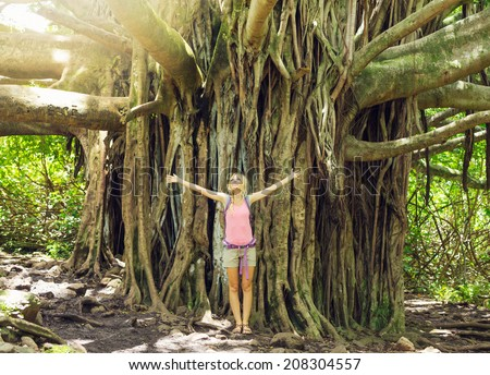 Attractive young woman having fun outdoors on hike, standing in front of giant banyan tree. - stock photo