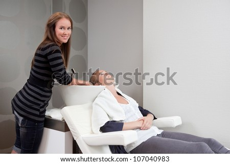 Attractive young woman having her hair washed at beauty salon - stock photo