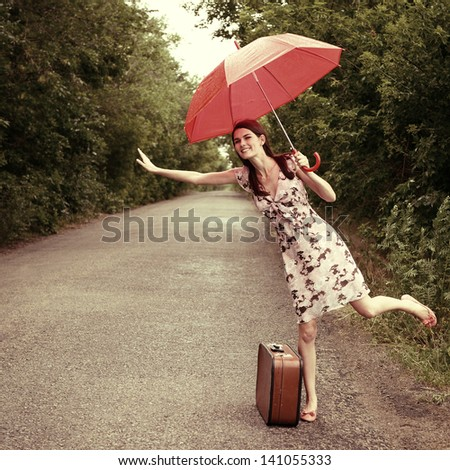 Attractive young woman hitchhiking along a road, toned, vintage stylization - stock photo