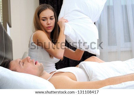 attractive young woman hits the pillow man, because he snores - stock photo