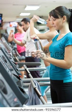 attractive young woman holding a bottle of water at the gym, needed refreshment - stock photo