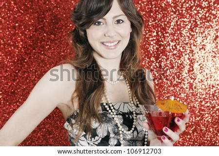 Attractive young woman holding a cocktail glass in a glittering red background at Christmas. - stock photo