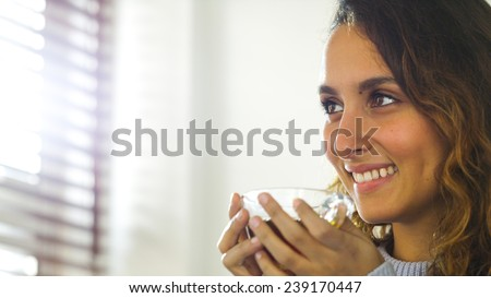Attractive young woman holding a hot drink in a kitchen in the morning light - stock photo