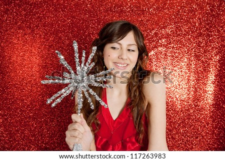 Attractive young woman holding a large christmas star while standing in front of a red glitter background smiling. - stock photo