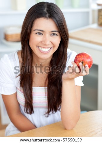 Attractive young woman holding a red an apple in kitchen - stock photo