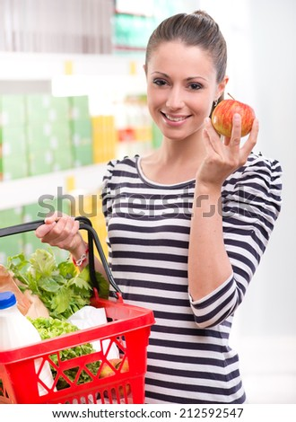 Attractive young woman holding an apple and smiling at supermarket. - stock photo