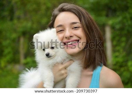 Attractive young woman holding german spitz puppy outside and smiling at camera. - stock photo