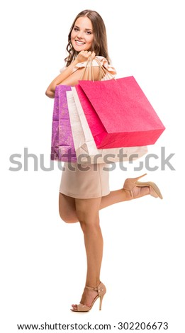 Attractive young woman holding shopping bags, looking at camera and smiling on white background. Side view. - stock photo