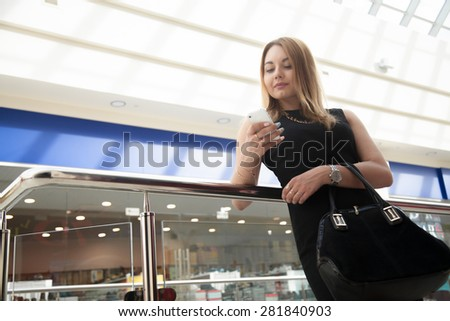 Attractive young woman holding suede handbag, wearing black dress making call, using app on cell phone, texting in shopping center - stock photo