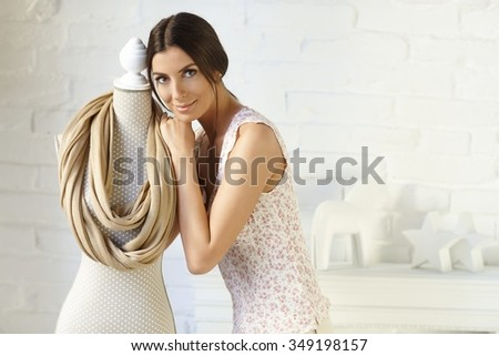 Attractive young woman hugging mannequin with favourite scarf, smiling, looking at camera. - stock photo