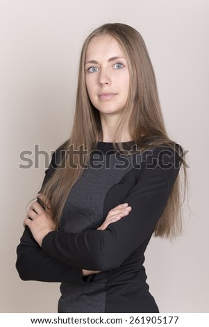Attractive young woman in a black dress looking at camera. - stock photo