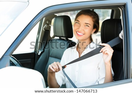 Attractive young woman in a car fastens seat belt  - stock photo